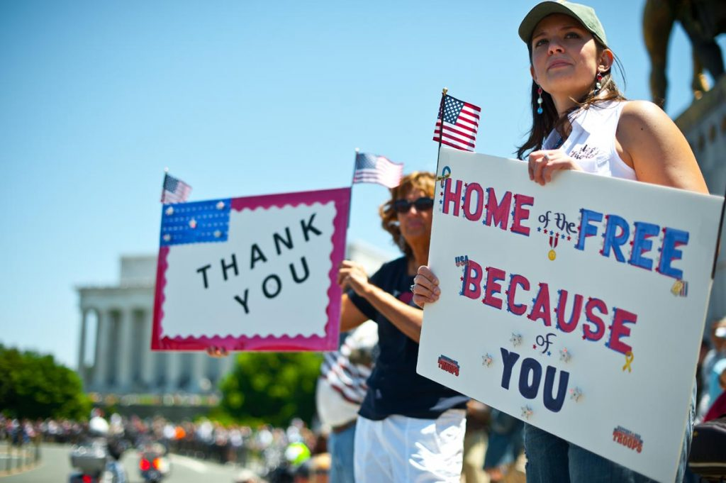 Two women hold up signs thanking the troops as members of the US military veterans' Rolling Thunder bikers group ride past in Washington on May 26, 2013 as the country marks Memorial Day. AFP PHOTO/Nicholas KAMMNICHOLAS KAMM/AFP/Getty Images ORG XMIT: US-VIETNA